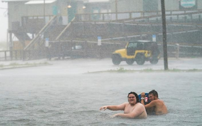 People play in a flooded car park at Navarre Beach in Pensacola Beach, Florida - Gerald Herbert /AP