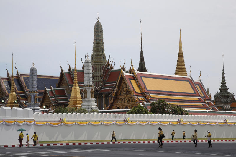 Thai people wearing the color of the king, yellow, to honor their King Maha Vajiralongkorn walk outside Grand Palace in Bangkok, Thailand, Saturday, May 4, 2019. Saturday began three days of elaborate centuries-old ceremonies for the formal coronation of Vajiralongkorn, who has been on the throne for more than two years following the death of his father, King Bhumibol Adulyadej, who died in October 2016 after seven decades on the throne. (AP Photo/Sakchai Lalit)
