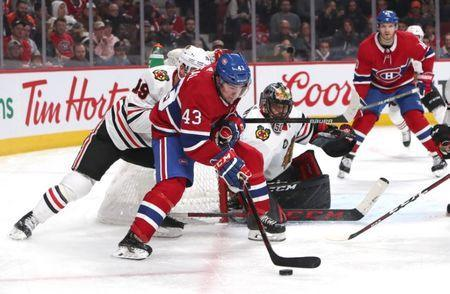 Mar 16, 2019; Montreal, Quebec, CAN; Montreal Canadiens center Michael Chaput (43) plays the puck against Chicago Blackhawks center Jonathan Toews (19) next to goaltender Corey Crawford (50) during the third period at Bell Centre. Mandatory Credit: Jean-Yves Ahern-USA TODAY Sports