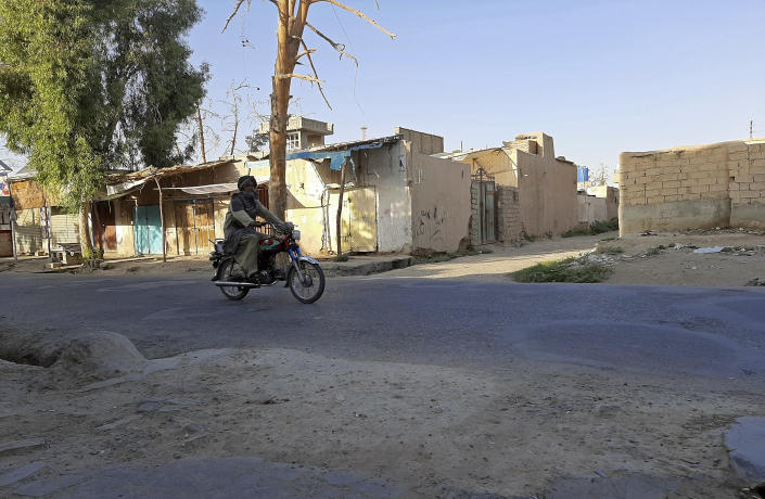 An Afghan man ride motorcycle on a deserted street during fighting between Taliban and Afghan security forces, in Lashkar Gah, Helmand province, southern Afghanistan, Tuesday, Aug. 3, 2021. U.S. and Afghan airstrikes were hitting Taliban targets in southern Helmand province on Wednesday, officials said, in an effort to dislodge the insurgents a day after they captured much of the provincial capital of Lashkar Gah. (AP Photo/Abdul Khaliq)