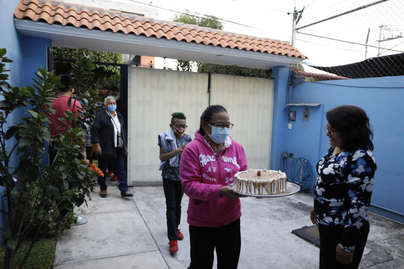 Marta Patricia Hernandez Santos, right, welcomes her sister's family and her mother, as they arrive for a small gathering at home to mark the 15th birthday of her daughter, Ximena Canejo Hernandez, in Tlalnepantla, just outside Mexico City, Monday, July 13, 2020. Another sister, a nurse in a COVID-19 hospital, did not attend to reduce the risk of coronavirus spread. Ximena's family, wanting to give her a traditional Quinceanera, had booked a church and event hall for July 18th long before the coronavirus pandemic hit, but the celebration had to be postponed until late November. (AP Photo/Rebecca Blackwell)