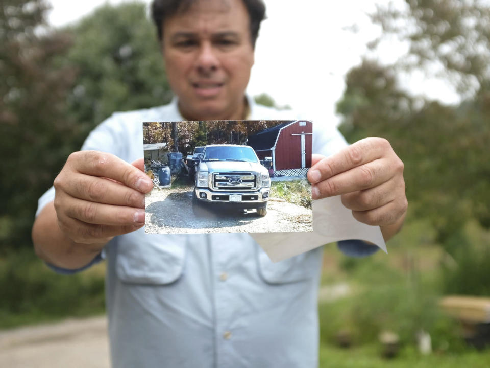 In thiis undated image provided by the Institute for Justice, Gerardo Serrano holds a photo of his pickup truck. Serrano ticked off the border crossing agents by taking some photos on his phone. So they took his pickup truck and held onto it for more than two years. Only after Serrano filed a federal lawsuit did he get back his Ford F-250. Now he wants the Supreme Court to step in and require a prompt court hearing as a matter of constitutional fairness whenever federal officials take someone's property under civil forfeiture law.(Institute for Justice via AP)