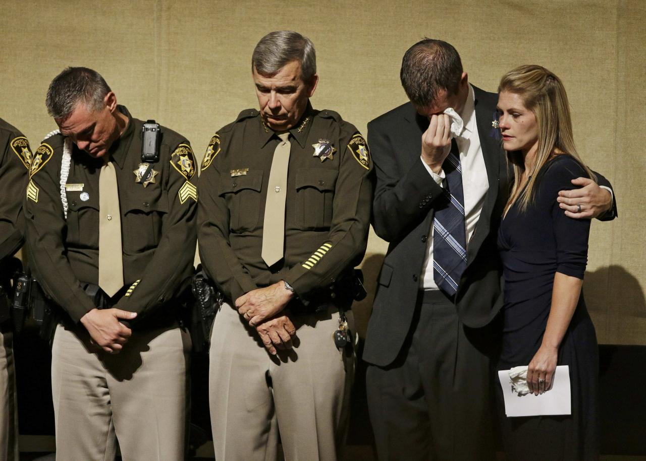 Sgt. Jimmy Oaks, Clark County Sheriff Doug Gillespie, Joseph Beck and Elizabeth Krmpotich (L to R) attend a memorial service for slain Las Vegas Metropolitan Police Officer Alyn Beck in Las Vegas June 14, 2014. Two suspects shot and killed Beck, 41, and fellow police officer Igor Soldo, 31, in an ambush at a Las Vegas restaurant June 8, 2014, before fatally shooting a third person inside a nearby Wal-Mart, authorities said. REUTERS/John Locher/Pool (UNITED STATES - Tags: OBITUARY)