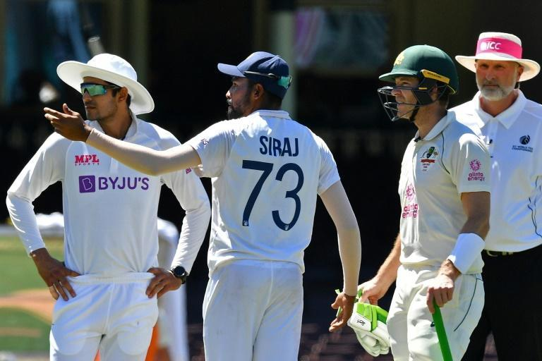 Flashpoint: India's Mohammed Siraj with Australia captain Tim Paine after the third Test was halted due to alleged racist remarks from fans