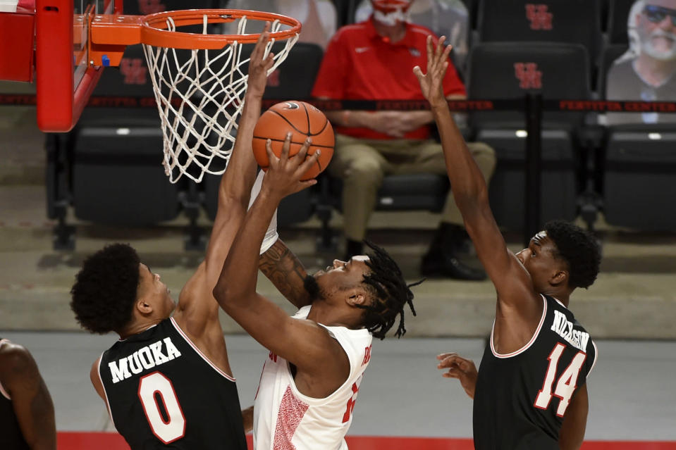 Houston forward J'Wan Roberts, center, shoots as Lamar center David Muoka (0) and forward Corey Nickerson (14) defend during the second half of an NCAA college basketball game, Wednesday, Nov. 25, 2020, in Houston. (AP Photo/Eric Christian Smith)