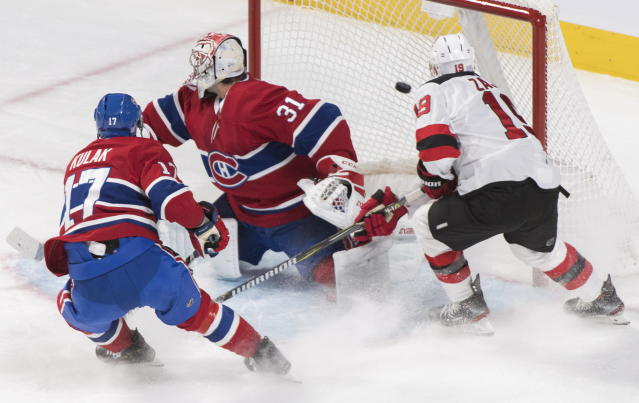 New Jersey Devils' Travis Zajac (19) scores against Montreal Canadiens goaltender Carey Price as Canadiens' Brett Kulak (17) defends during first-period NHL hockey game action in Montreal, Thursday, Nov. 28, 2019. (Graham Hughes/The Canadian Press via AP)