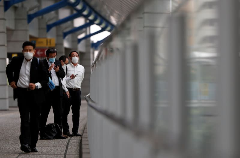 Businessmen wearing protective face masks are seen on a pedestrian bridge in a business district in Tokyo