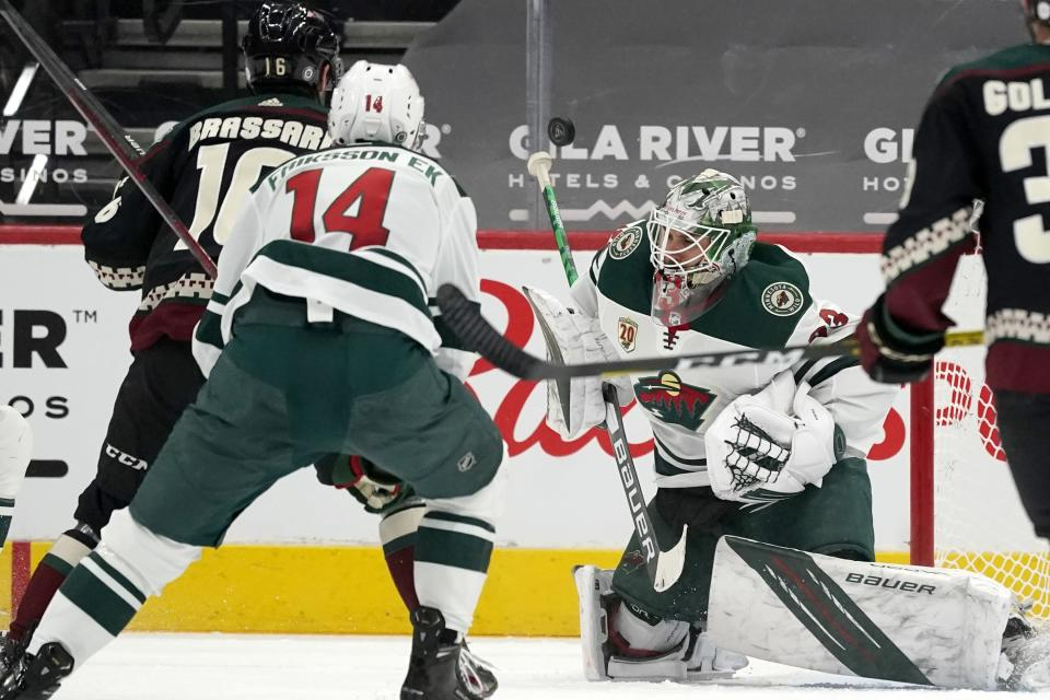 Minnesota Wild goaltender Cam Talbot, right, has a shot go off his stick as Arizona Coyotes center Derick Brassard (16) and Wild center Joel Eriksson Ek (14) look on during the second period of an NHL hockey game Wednesday, April 21, 2021, in Glendale, Ariz. (AP Photo/Ross D. Franklin)