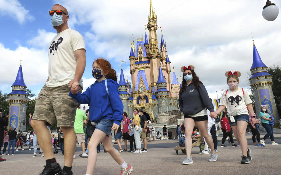 FILE - IN this Dec. 21, 2020 file photo, A family walks past Cinderella Castle in the Magic Kingdom, at Walt Disney World in Lake Buena Vista, Fla. Florida's major theme parks are adjusting their face mask policies after the federal government loosened its recommendations as more people get vaccinated for the coronavirus. Visitors to Walt Disney World and Universal Studios-Orlando were allowed Saturday, May 15, 2021 to remove their masks when they are outdoors except when they are on attractions, in line or riding a tram or other transportation.(Joe Burbank/Orlando Sentinel via AP, File)