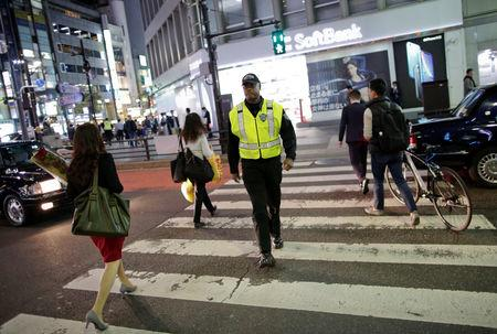 Japanese security firm Executive Protection Inc. employee 59-year-old Antonio Nathaniel King of the U.S. patrols on the street at Roppongi shopping and amusement district in Tokyo, Japan November 1, 2018. Picture taken November 1, 2018.  REUTERS/Issei Kato