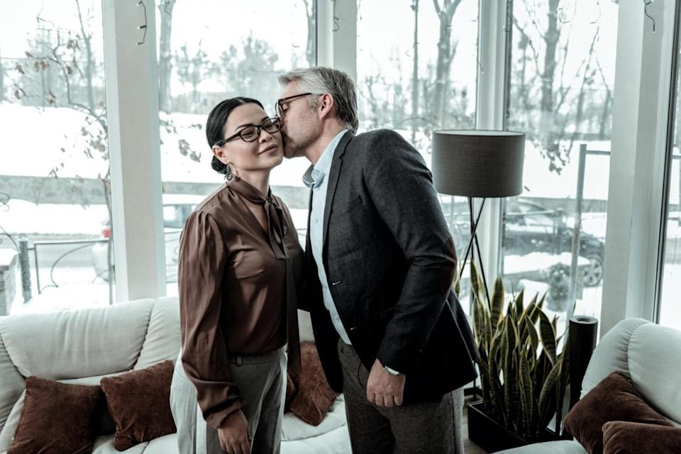 Kiss on a cheek. Tall grey-haired handsome man wearing a blue shirt kissing a woman on a cheek