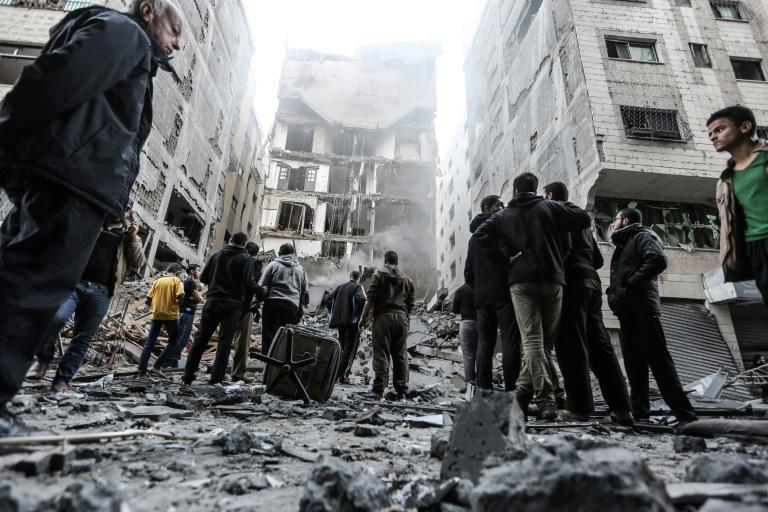 Palestinians gather in Gaza City early on November 13, 2018, outside buildings damaged by overnight air strikes