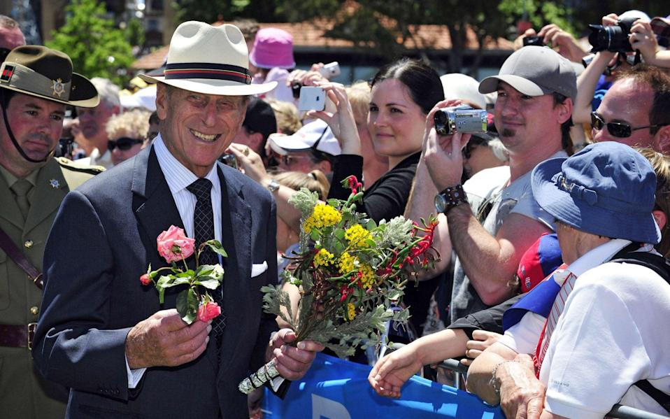 Britain's Prince Philip (L) receives flowers as he meets with wellwishers gathered in Perth for a 'Great Aussie Barbecue' event