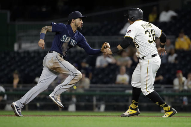 Seattle Mariners shortstop J.P. Crawford, left, tags out Pittsburgh Pirates' Jose Osuna (36) between first and second during the ninth inning of a baseball game in Pittsburgh, Tuesday, Sept. 17, 2019. The Mariners won 6-0. (AP Photo/Gene J. Puskar)