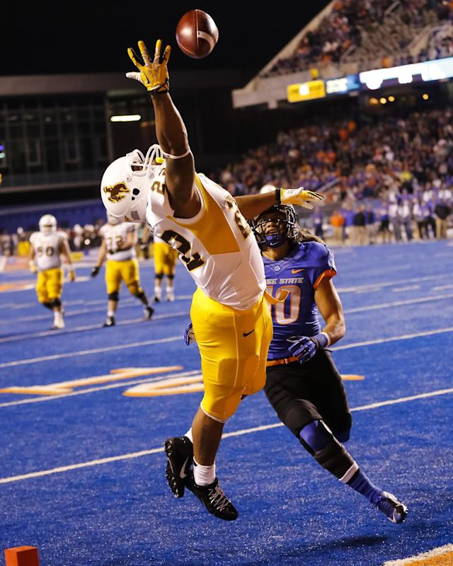 Wyoming running back Tedder Easton (22) just misses a pass over Boise State safety Jeremy Ioane (10) during the first half of an NCAA college football game in Boise, Idaho, Saturday, Nov. 16, 2013. (AP Photo/Otto Kitsinger)
