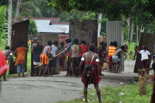 Papuan tribal warriors from Amole village (foreground) clash with tribes from Harapan village
