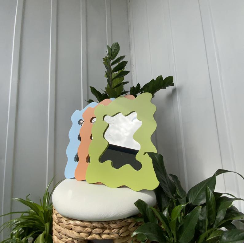 """<h2>Lime Green Wavy Mirror</h2><br>""""I just moved into a new apartment last month and have slowly but surely been decorating it. I've been seeing these funky mirrors everywhere and finally decided to snag one of my own to prop up on my nightstand. It shipped quickly, the quality is great, and the seller answered my questions in a timely manner — it also adds some character to my otherwise boring white room!"""" <em>— Elizabeth Gulino, Health & Wellness Writer </em><br><br><strong>YeshiX2</strong> Lime Green Wavy Mirror, $, available at <a href=""""https://go.skimresources.com/?id=30283X879131&url=https%3A%2F%2Fwww.etsy.com%2Flisting%2F990989777%2Fwavy-mirror-cloud-mirror-lime-green"""" rel=""""nofollow noopener"""" target=""""_blank"""" data-ylk=""""slk:Etsy"""" class=""""link rapid-noclick-resp"""">Etsy</a>"""