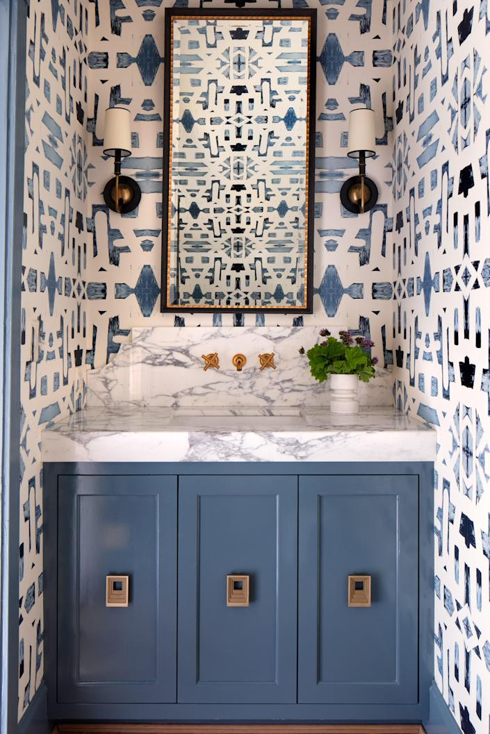 In the powder room, a soothing blue Indigo Ocean Alta Non-Woven wallpaper by Lindsay sets a calming tone. A custom vanity is bejeweled in Nest Studio pulls, and Circa Lighting sconces flank a custom mirror.
