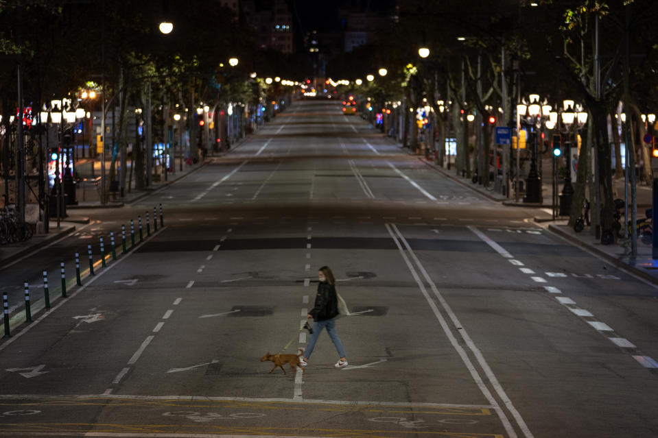 A resident walks with a dog on an empty street after curfew in Barcelona on Sunday, Oct. 25, 2020. Spain orders nationwide curfew to stem worsening outbreak. Spanish Prime Minister Pedro Sánchez has declared a second nationwide state of emergency in hopes of stemming a resurgence in coronavirus infections. (AP Photo/Emilio Morenatti)