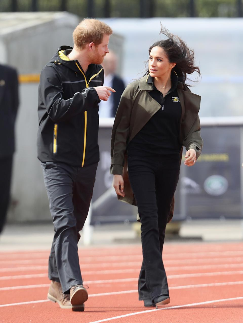 """<p>On Friday, the couple dressed down to attend the Invictus Games tryouts in Bath. For the event, 36-year-old Markle wore a Invictus Games polo shirt paired with black bootcut jeans by Mother Denim. She kept warm in a <a rel=""""nofollow noopener"""" href=""""https://www.aritzia.com/en/product/bascom-trench-coat/65544.html?dwvar_65544_color=5091"""" target=""""_blank"""" data-ylk=""""slk:chic $195 trench coat"""" class=""""link rapid-noclick-resp"""">chic $195 trench coat</a> by one of her favourite (Canadian!) brands, Babaton. </p>"""