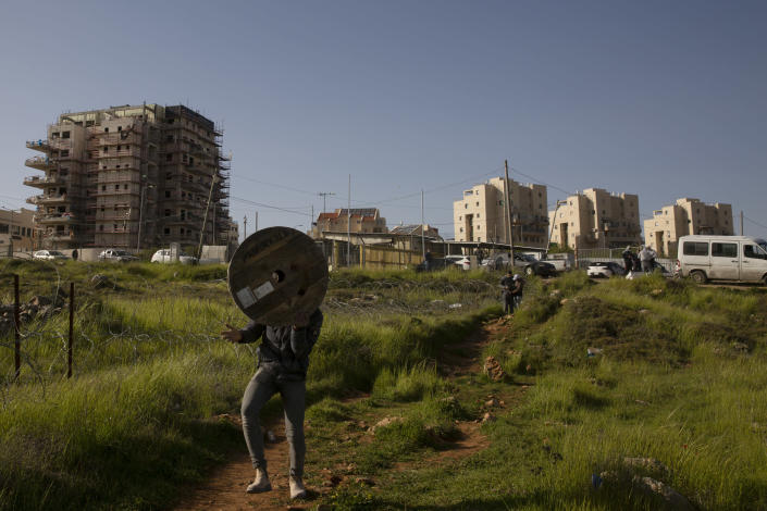 A Palestinian man carries an empty spool from the construction site where he works on a new building in the West Bank Jewish settlement of Efrat, Tuesday, March 16, 2021. Israel went on an aggressive settlement spree during the Trump era, according to an AP investigation, pushing deeper into the occupied West Bank than ever before and putting the Biden administration into a bind as it seeks to revive Mideast peace efforts. (AP Photo/Maya Alleruzzo)
