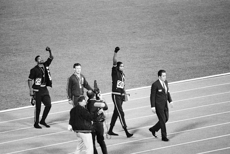 (Original Caption) 1968-Mexico City, Mexico- Tommie Smith, center, and John Carlos, right, of the United States, raise gloved hands after receiving their Olympic Medals for finishing first and third rspectively in the men's 200-meter in 1968 Olympics in Mexico City Oct. 16. Second place Peter Norman of Australia is at left. Smith's winning time of 19.8 secods broke world and Olympic records.