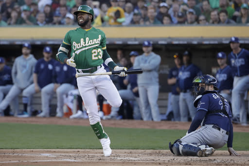 Oakland Athletics' Jurickson Profar (23) reacts after avoiding a pitch in front of Tampa Bay Rays catcher Travis d'Arnaud during the first inning of an American League wild-card baseball game in Oakland, Calif., Wednesday, Oct. 2, 2019. (AP Photo/Jeff Chiu)