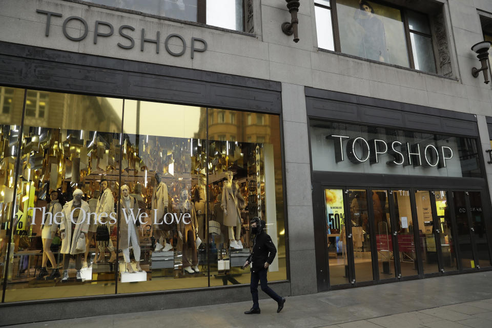 A person wearing a face mask to try to curb the spread of coronavirus walks past the temporarily closed Topshop flagship store on Oxford Street, during England's second coronavirus lockdown, in London, Monday, Nov. 30, 2020. Arcadia Group, the retail empire of tycoon Philip Green, which owns well-known British fashion chains like Topshop and employs around 15,000 people, appears to be on the brink of collapse following the economic shock of the coronavirus pandemic. (AP Photo/Matt Dunham)