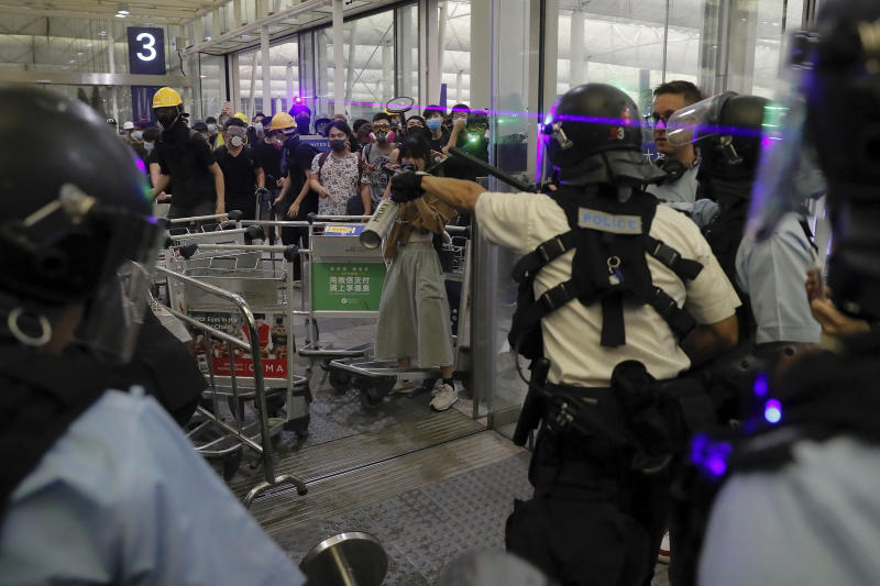 Policemen in riot gears face protesters at the main entrance of the airport during a demonstration in Hong Kong, Tuesday, Aug. 13, 2019. Chaos has broken out at Hong Kong's airport as riot police moved into the terminal to confront protesters who shut down operations at the busy transport hub for two straight days. (AP Photo/Kin Cheung)
