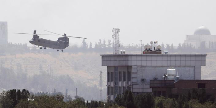 A U.S. Chinook helicopter flies near the U.S. Embassy in Kabul, Afghanistan, Sunday, Aug. 15, 2021. Helicopters are landing at the U.S. Embassy in Kabul as diplomatic vehicles leave the compound amid the Taliban advanced on the Afghan capital.