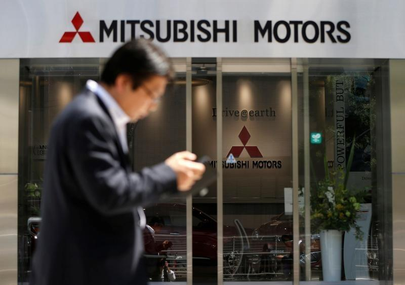 A man walks in front of an entrance of Mitsubishi Motors Corp's headquarters in Tokyo, Japan