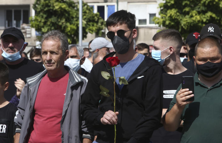 A young man holds a rose during a march to honor the victims in the burned out makeshift hospital in North Macedonia's northwestern town of Tetovo, Saturday, Sept. 11, 2021. Hundreds of people have marched Saturday in northwestern town of Tetovo to honor their 14 countrymen killed in a deadly fire that broke earlier this week and destroyed COVID-19 field hospital. (AP Photo/Boris Grdanoski)