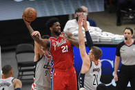 Philadelphia 76ers center Joel Embiid (21) looks to pass the ball as Washington Wizards forward Deni Avdija (9) and center Moritz Wagner (21) defend during the first half of an NBA basketball game, Friday, March 12, 2021, in Washington. Avdija was called for a foul on the play. (AP Photo/Nick Wass)