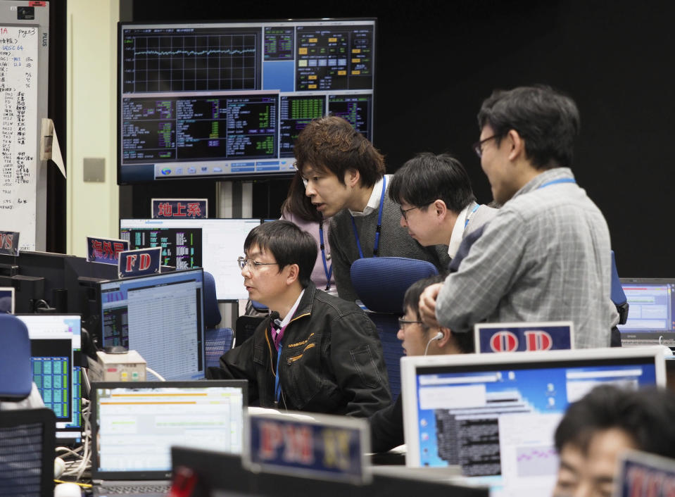 FILE - In this Feb. 21, 2019, file photo provided by the Japan Aerospace Exploration Agency JAXA, staff of the Hayabusa2 Project watch monitors for a safety check at the control room of the JAXA Institute of Space and Astronautical Science in Sagamihara, near Tokyo. The Japanese government said Tuesday that Tokyo police are investigating cyberattacks on about 200 companies and research organizations in Japan, including one on the country's JAXA space agency by a hacking group linked to the Chinese military. (ISAS/JAXA via AP, File)