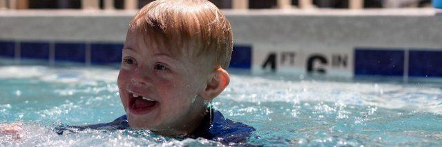 Boy with Down syndrome swimming in pool, smiling