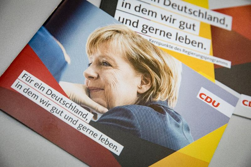 A portrait of German Chancellor and leader of the Christian Democratic Union party (CDU) Angela Merkel is seen on a leaflet at the CDU's headquarters in Berlin, ahead of general elections (AFP Photo/AXEL SCHMIDT)