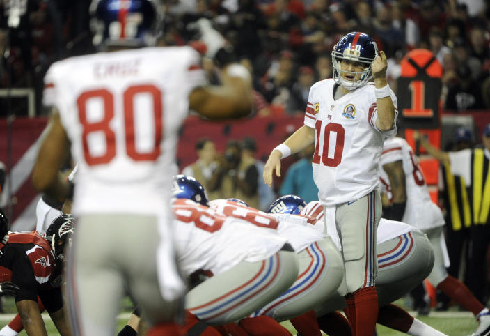New York Giants quarterback Eli Manning (10) speaks to New York Giants wide receiver Victor Cruz (80) against the Atlanta Falcons during the first half of an NFL football game, Sunday, Dec. 16, 2012, in Atlanta. (AP Photo/John Amis)