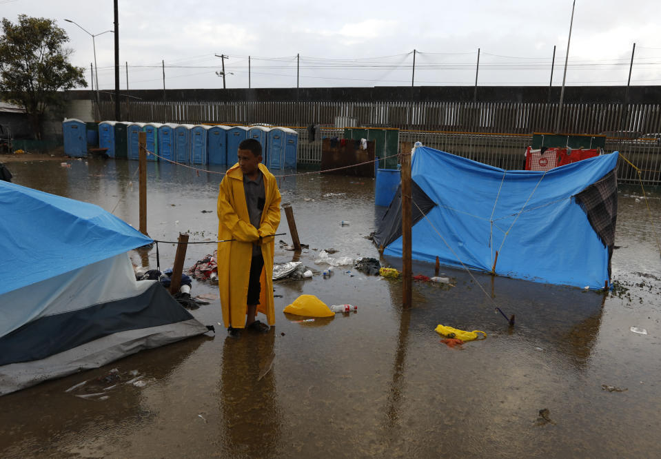 A boy examines a flooded tent between bouts of heavy rain at a sports complex sheltering thousands of Central Americans in Tijuana, Mexico, Thursday, Nov. 29, 2018. Aid workers and humanitarian organizations expressed concerns Thursday about the unsanitary conditions at the sports complex in Tijuana where more than 6,000 Central American migrants are packed into a space adequate for half that many people and where lice infestations and respiratory infections are rampant.(AP Photo/Rebecca Blackwell)