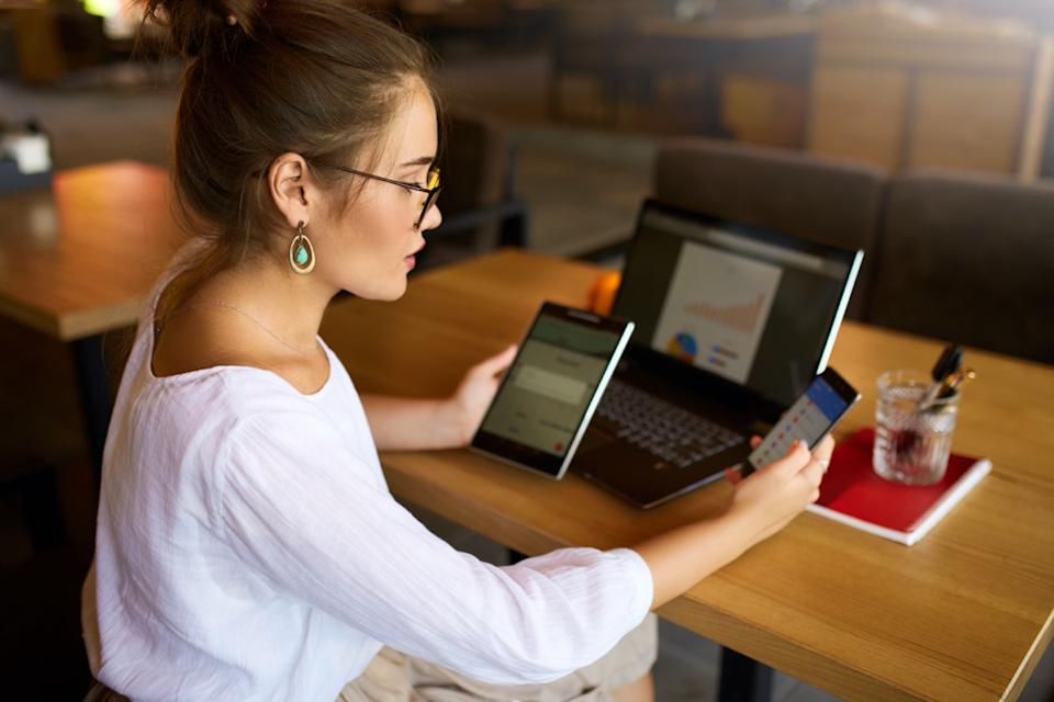 woman in glasses working with multiple electronic internet devices