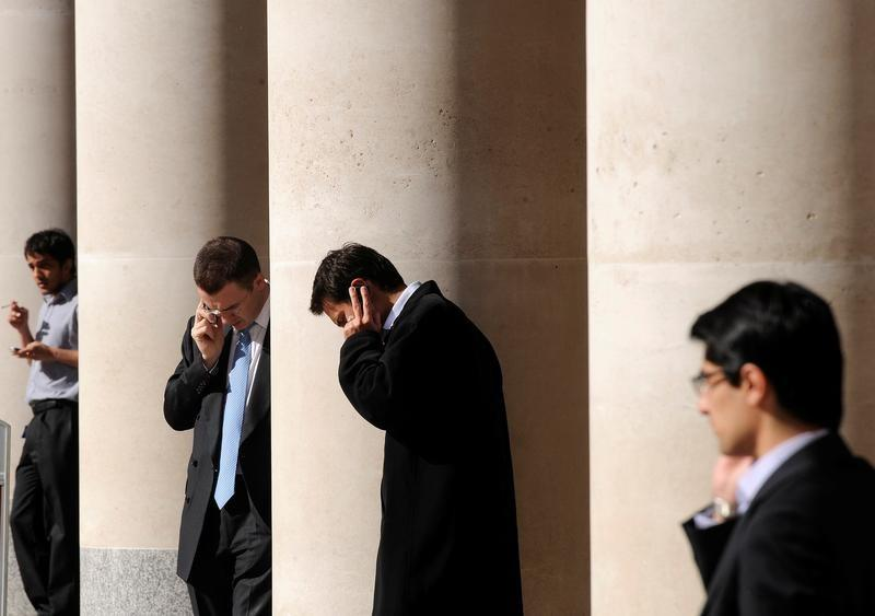 City workers make phone calls outside the London Stock Exchange in Paternoster Square in the City of London, Britain, October 1, 2008. REUTERS/Toby Melville/File Photo