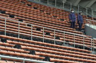 Police officers stand guard at empty seats of the grandstand during the unveiling ceremony for Olympic Flame of the Tokyo 2020 Olympic torch relay at Komazawa Olympic Park, Friday, July 9, 2021, in Tokyo. Komazawa Olympic Park, where the flame unveiling ceremony took place, was used as one of the venues during the previous Tokyo Olympics held in 1964.(AP Photo/Eugene Hoshiko)