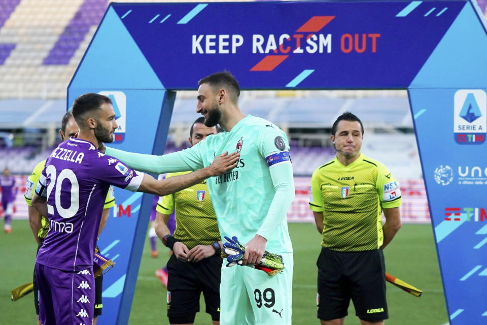 """AC Milan's goalkeeper Gianluigi Donnarumma, center, and Fiorentina's German Pezzella, left, greet each other under a banner reading """"Keep racism out"""" as part of the new anti-racism campaign launched last Sunday by the Italian soccer League, prior to a Serie A match between Fiorentina and AC Milan at the Artemio Franchi stadium in Florence, Italy, Sunday, March 21, 2021. Serie A's efforts to combat racism inside its stadiums was in shambles little more than a year ago when league CEO Luigi De Siervo decided to take matters into his own hands. (Spada/LaPresse via AP)"""