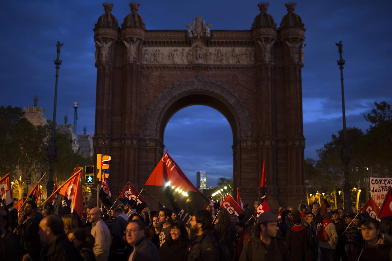 Demonstrators walk past the Arch of Triumph as they march during a protest in Barcelona.
