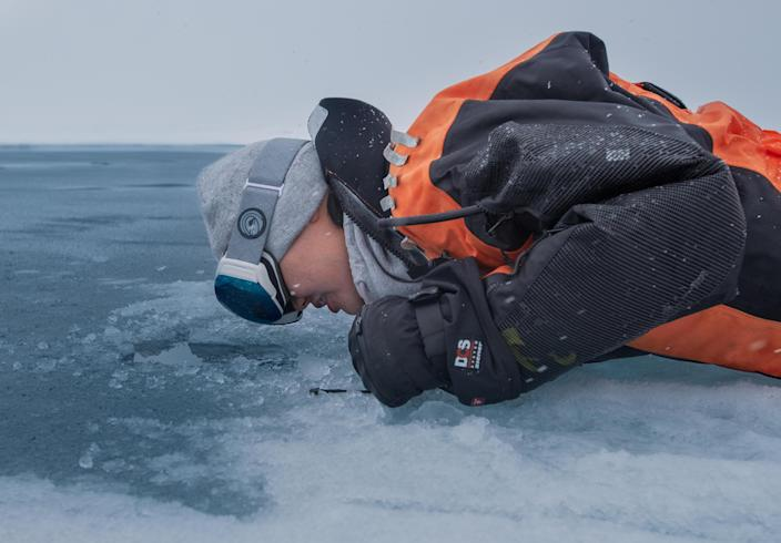 Researcher Dr. Alison Fong peers through the Arctic Sea ice during a year-long mission aboard the RV Polarstern to evaluate the impact of climate change on the Arctic. / Credit: Alfred Wegener Insititute / Lianna Evans Nixon