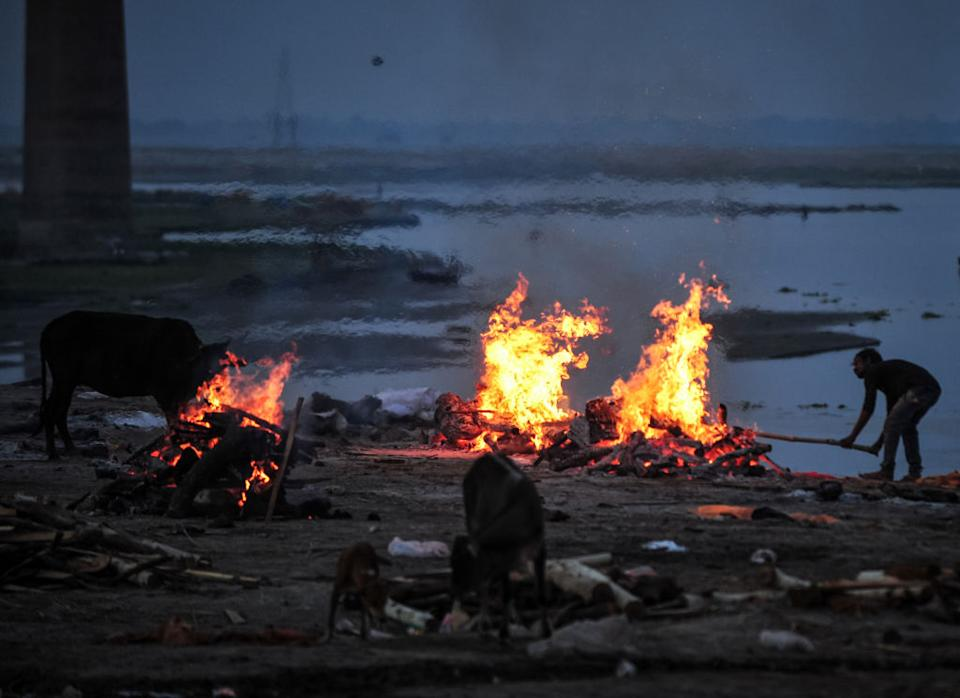 A crematorium worker cremates the unclaimed bodies of people who were thought to have died of Covid in a mass crematorium ground, on the banks of Ganges River on May 5. Source: Getty