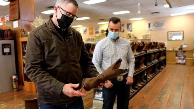 Finance Minister Travis Toews purchased new footwear to wear when presenting his 2021 budget at the Alberta Boot Company in Calgary.  (Paul Taillon/Office of the Premier  - image credit)