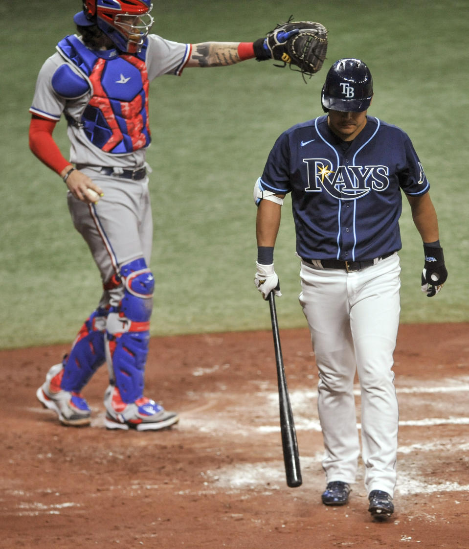 Texas Rangers catcher Jonah Heim gestures toward the mound as Tampa Bay Rays' Yoshi Tsutsugo walks to the dugout after striking out during the second inning of a baseball game Wednesday, April 14, 2021, in St. Petersburg, Fla. (AP Photo/Steve Nesius)