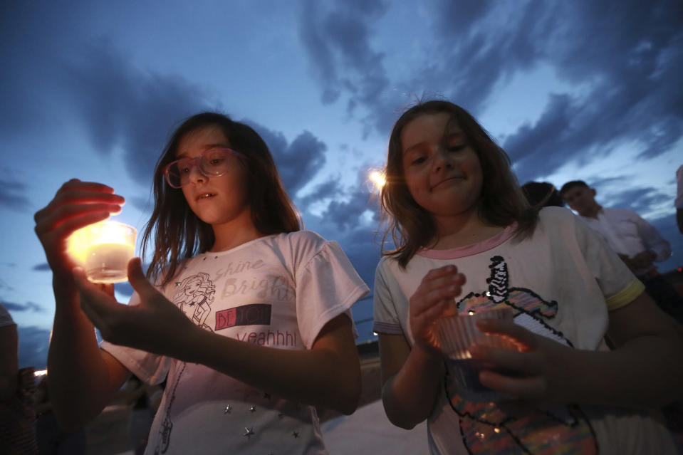 People gather in Juarez, Mexico, Saturday, Aug. 3, 2019, in a vigil for the 3 Mexican nationals who were killed in an El Paso shopping-complex shooting. Twenty people were killed and more than two dozen injured in a shooting Saturday in a busy shopping area in the Texas border town of El Paso, the state's governor said. (AP Photo/Christian Chavez)