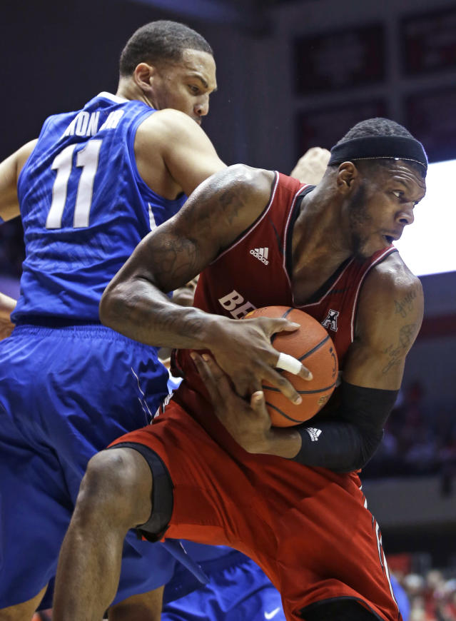 Cincinnati forward Titus Rubles pulls in a rebound against Memphis guard Michael Dixon Jr. (11) in the second half of an NCAA college basketball game, Thursday, March 6, 2014, in Cincinnati. Rubles scored 24 points in the game won by Cincinnati 97-84. (AP Photo/Al Behrman)