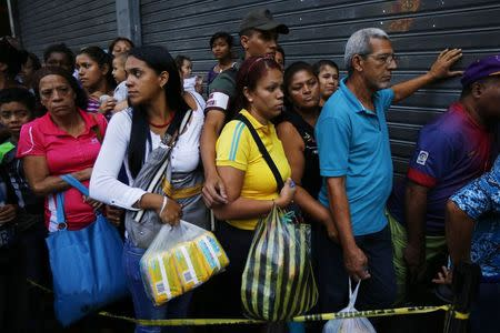 People line up to buy toilet paper and baby diapers at a supermarket in downtown Caracas January 19, 2015. REUTERS/Jorge Silva
